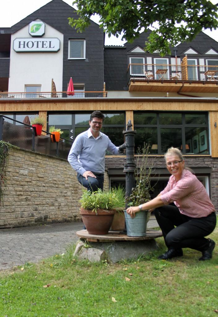 Annette und Jörg Treichel vor ihrem Biohotel am Brunnen in dem kleinen Garten. Foto: Silke Liebig-Braunholz