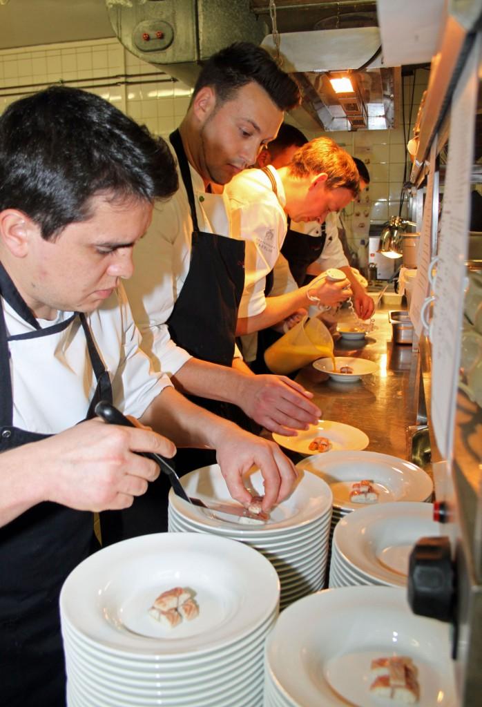 Letzte Handgriffe bevor die Teller serviert werden. Die Crew ist konzentriert bei der Arbeit  Foto: Liebig-Braunholz